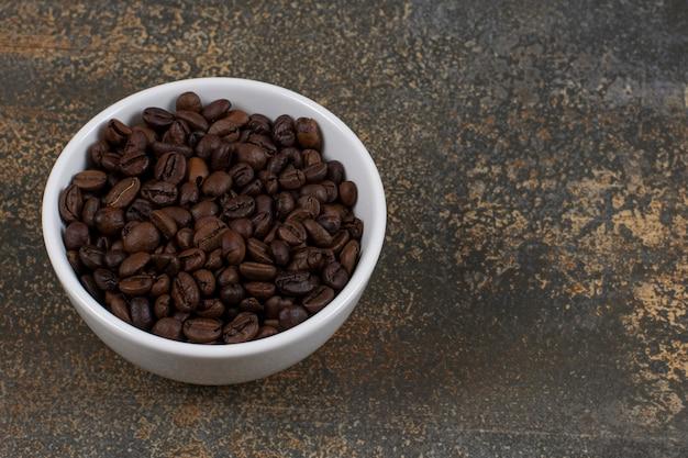 Granos de café aromáticos en un tazón blanco.