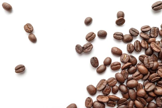 Granos de café asados aislados en el fondo blanco. de cerca.
