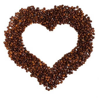 Granos de café asados en blanco. espacio para texto en forma de corazón.