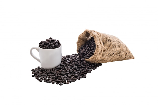Granos de café en bolsa y taza de café blanco.