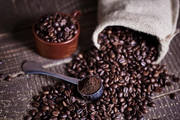 Granos de café y bolsa de yute en mesa de madera