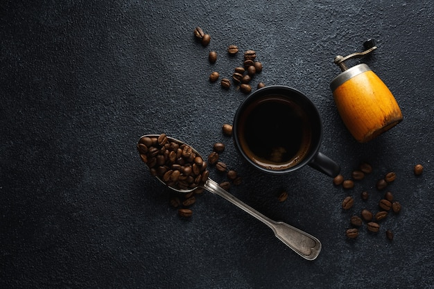 Granos de café, café y cuchara sobre superficie oscura
