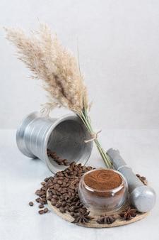 Granos de café y café molido en pieza de madera
