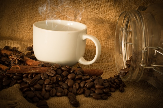 Granos de café y café de la taza en el saco de tela seleccionar enfoque, tono de color vintage o tono oscuro