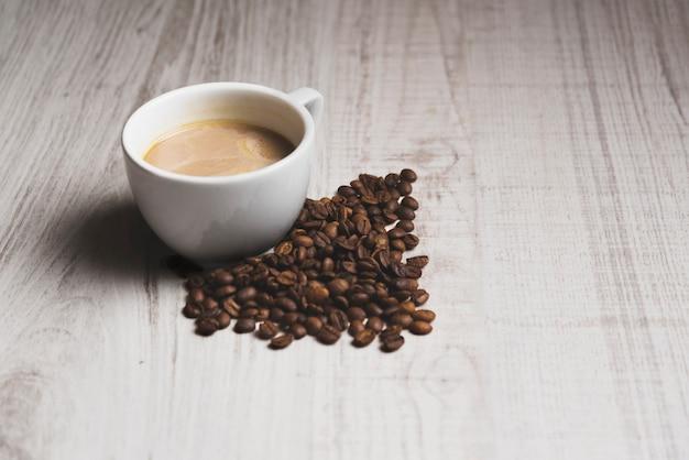 Granos de café cerca de la taza