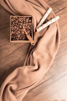 Granos de café y connamons en caja sobre mesa de madera