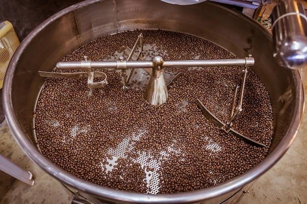 Granos de café crudos en máquina tostadora de plata