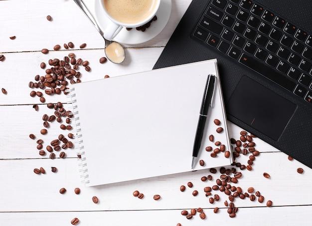 Granos de café en cuaderno en blanco, taza de café y portátil