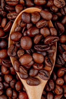 Granos de café en una cuchara de madera en granos de café vista cercana