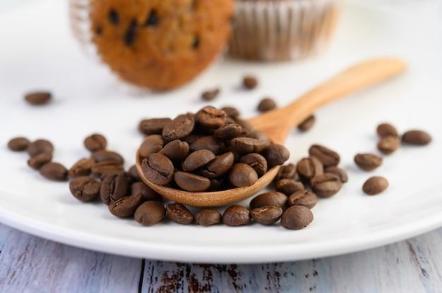 Granos de café en la cuchara de madera y pastelitos de plátano en una mesa de madera blanca.