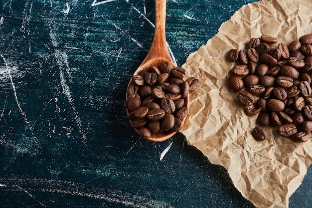 Granos de café en una cuchara de madera y sobre el papel.