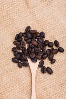 Granos de café en cuchara de madera con yute