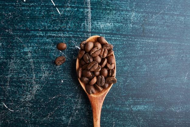 Granos de café en una cuchara de madera.