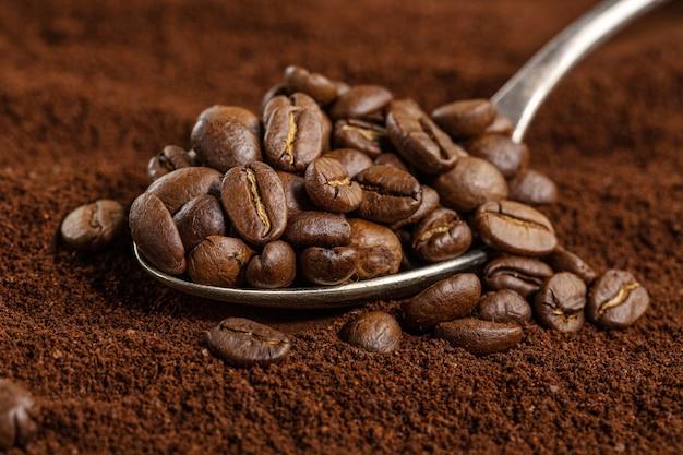 Granos de café en cuchara sobre café molido. de cerca.