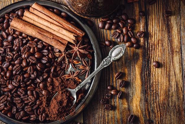 Granos de café con cucharada de café molido, canela en rama y anís estrellado chino sobre placa de metal. algunos frijoles esparcidos sobre la mesa de madera
