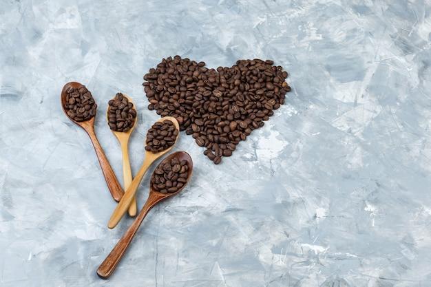 Los granos de café en cucharas de madera planas yacían sobre un fondo de yeso gris