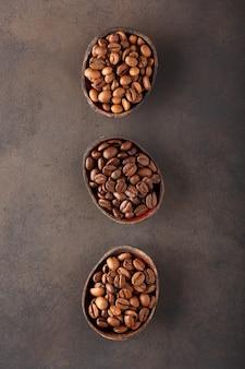 Granos de café de diferentes variedades y tostados diferentes en tres tazones de madera.