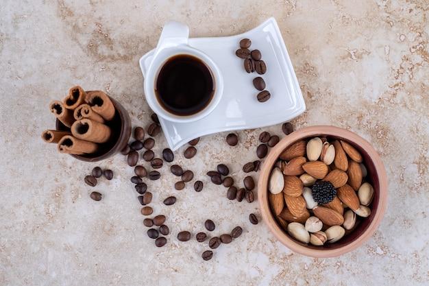 Granos de café esparcidos, frutos secos variados, ramitas de canela y una taza de café