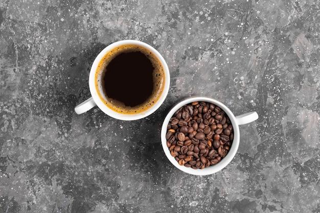 Granos de café y espresso en tazas blancas sobre fondo gris