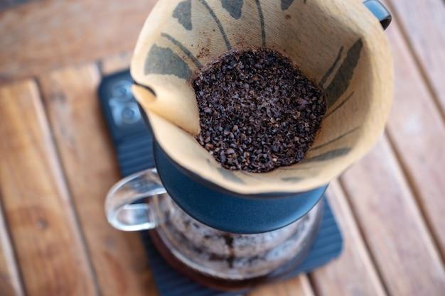 Granos de café en el filtro de papel en la balanza de café digital mientras se hace un goteo de café en la mesa de madera vintage