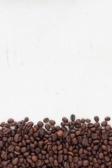 Granos de café en el fondo de madera blanca de grano