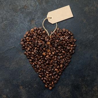 Granos de café en forma de corazón en rústico oscuro