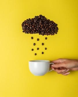 Granos de café en forma de nube lluviosa con taza blanca sobre superficie amarilla.