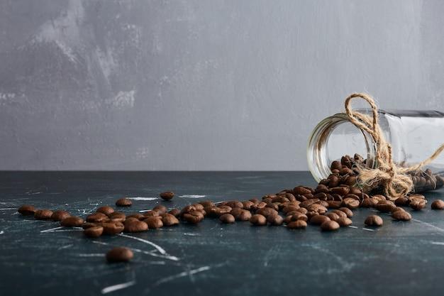 Granos de café de un frasco de vidrio.