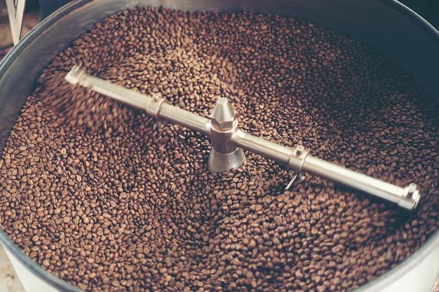Granos de café frescos en la máquina de asar, café tostado arabica