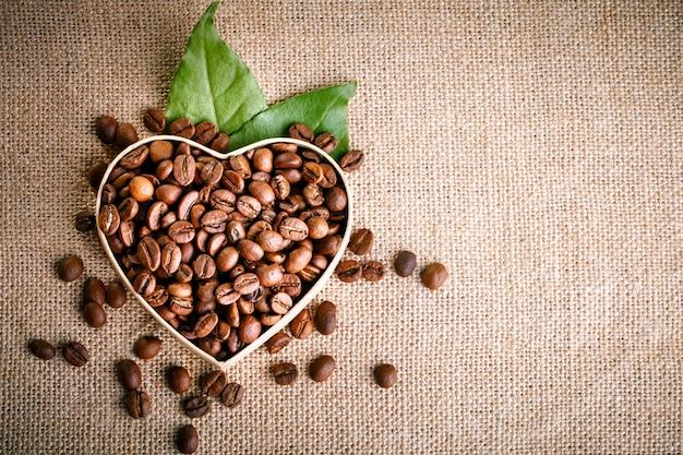 Granos de café fritos se encuentran en forma de corazón en tablas de madera y arpillera.