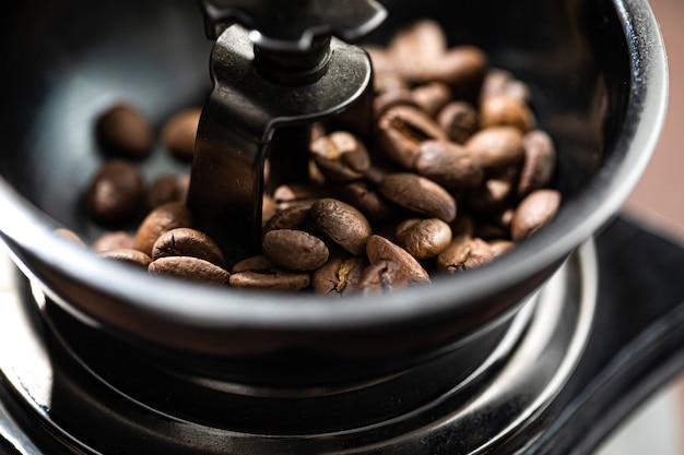 Los granos de café fritos se encuentran en un molinillo de café. el café árabe se reza en un molinillo de café mecánico. cafe mañanero.