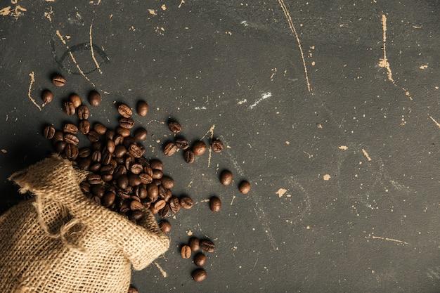 Granos de café fritos negros sobre fondo oscuro con textura