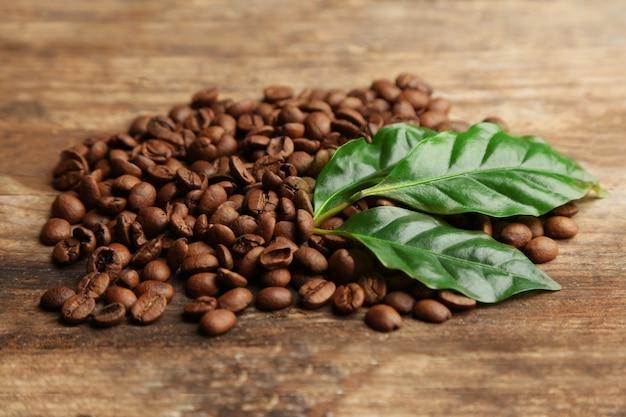 Granos de café y hojas verdes en madera
