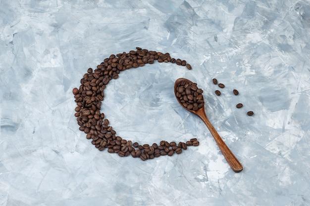 Granos de café laicos planos en cuchara de madera sobre fondo de yeso gris. horizontal