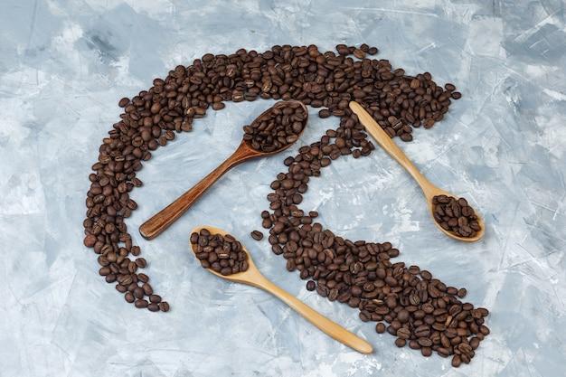 Granos de café laicos planos en cucharas de madera sobre fondo de yeso gris. horizontal