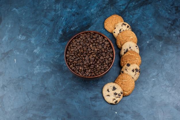 Granos de café laicos planos en un tazón con diferentes tipos de galletas sobre fondo azul oscuro. horizontal