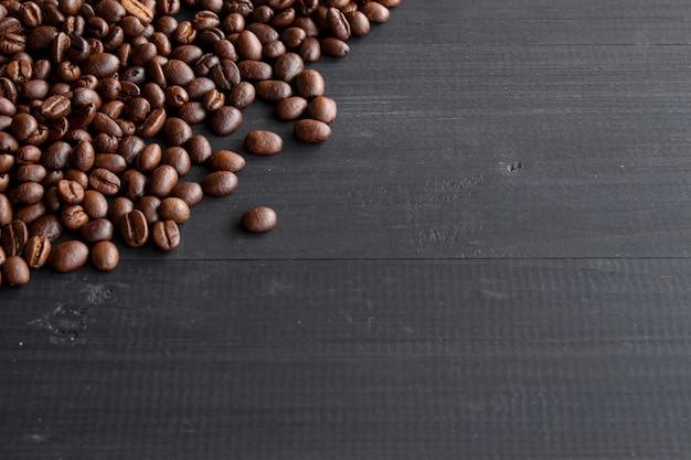Granos de café en madera vieja con enfoque suave y luz en el fondo