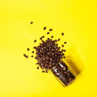Granos de café en mesa amarilla, endecha plana, vista superior