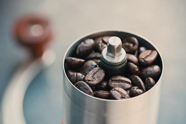 Granos de café en un molinillo de mano, primer plano de granos de café tostados en un molinillo de café manual