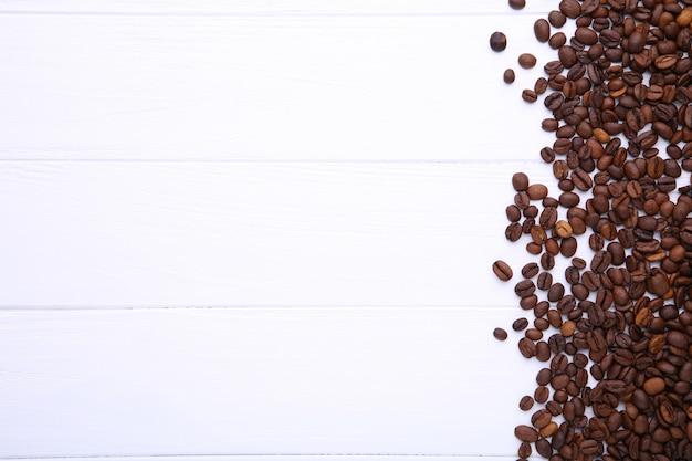 Granos de café naturales en el fondo de madera blanco
