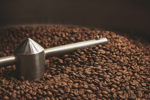Granos de café oscuro, aromático, chocolate recién horneado y amanecer fresco caliente dentro de la mejor máquina tostadora profesional