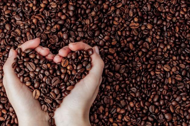 Granos de café en palmas de hombre en forma de corazón en el café.