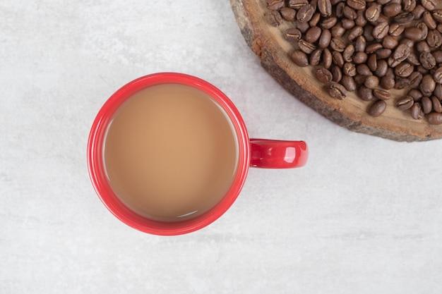 Granos de café en la pieza de madera con una taza de café roja
