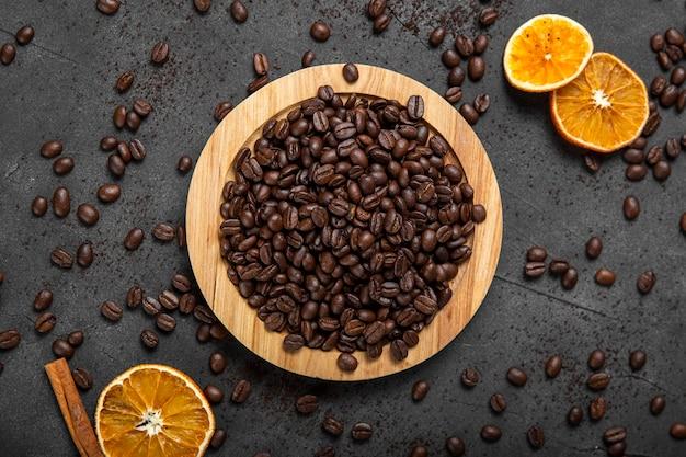 Granos de café planos sobre tabla de madera