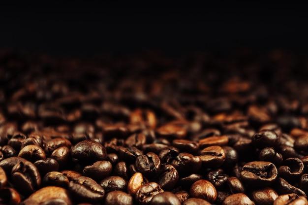 Los granos de café planos yacían sobre una mesa de madera sobre un fondo negro. clave baja. copie el espacio.
