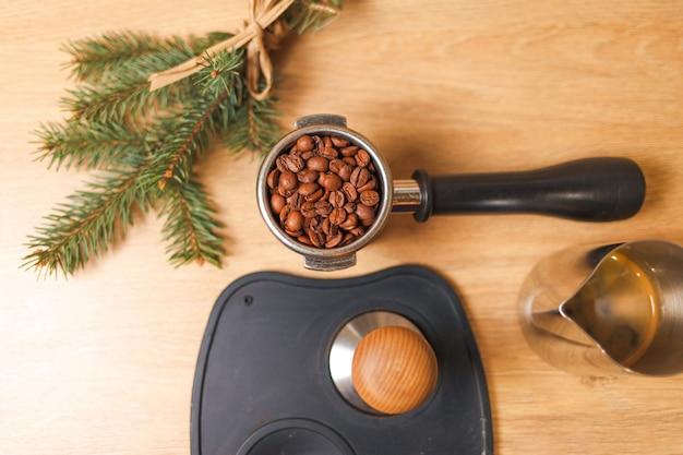 Granos de café en portafiltro, sabotaje y rama de árbol.