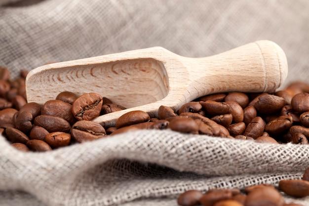 Granos de café con los que puede hacer una bebida de café caliente y vigorizante, granos de café marrón sobre una mesa hecha de tablas