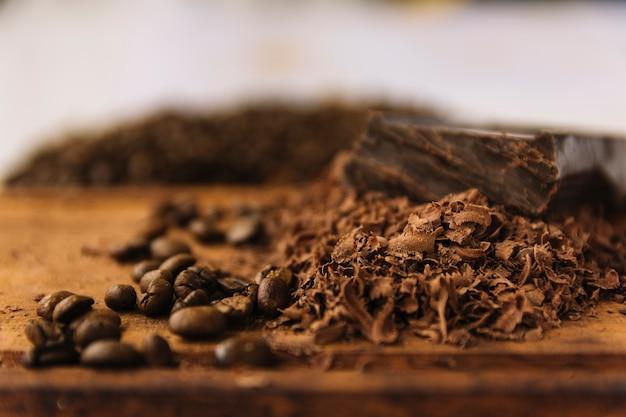 Granos de café y rizos de chocolate en la tabla de cortar