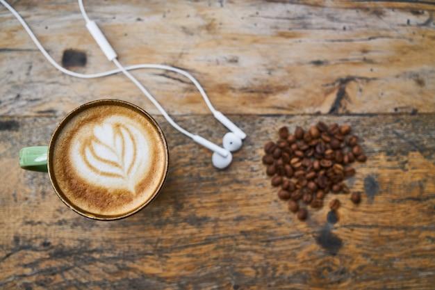 Granos de café rosted y auriculares en una mesa