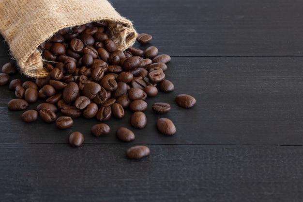 Granos de café en saco de arpillera en madera vieja con enfoque suave y luz en el fondo